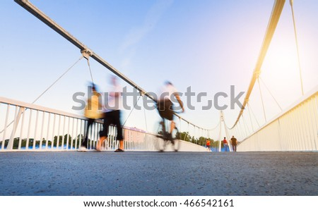 Image of motion of people walking and riding bikes on a pedestrian bridge
