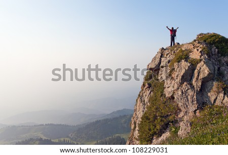 Image of mountain scenery, on top of which stands the silhouette of a tourist with his hands up, who enjoys success achieved heavy climbing. - stock photo