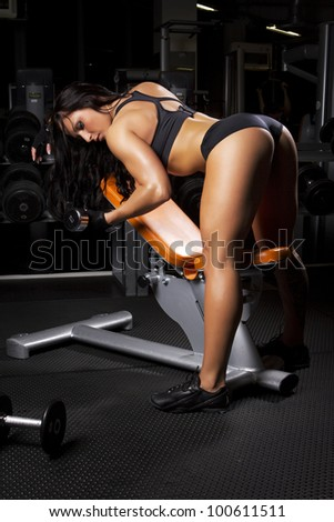 Image of muscle woman doing exercises in gym