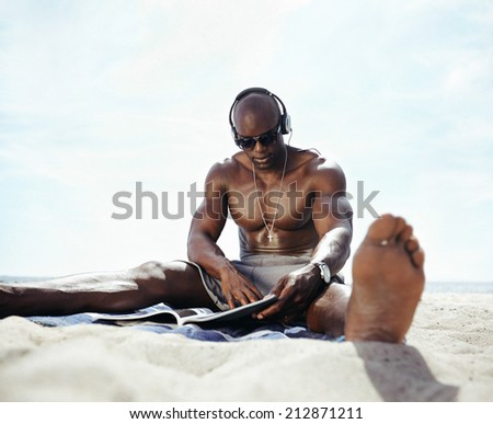 Image of muscular young man sitting on beach wearing headphones reading a magazine. African guy relaxing on beach on summer day. - stock photo