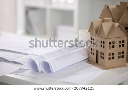 Image of new model house on architecture blueprint plan at desk - stock photo