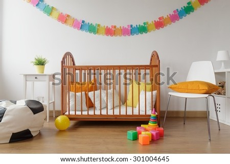 Image of newborn bright bedroom with wooden crib - stock photo