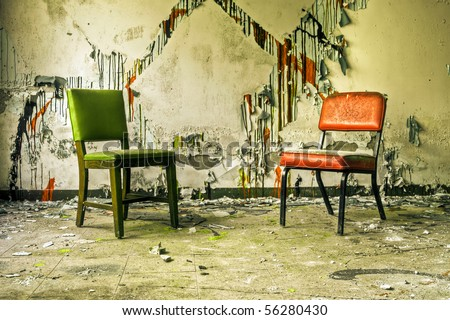Image of old chairs in an abandoned building with cracked and peeling paint illuminated by natural daylight.