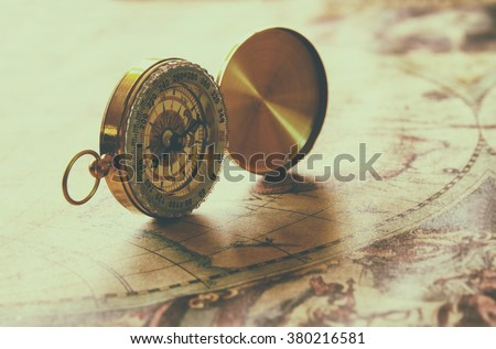image of old compass on vintage map. vintage filtered and toned - stock photo