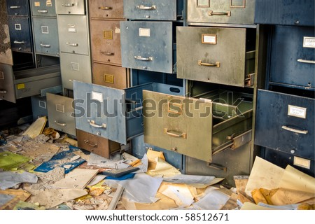 Image of old rusty filing cabinets in a derelict abandoned building with files scattered on the floor. - stock photo
