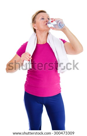 Image of old senior woman in sport outfit with white towel on her neck drinking water, isolated on white background, Positive human emotions - stock photo