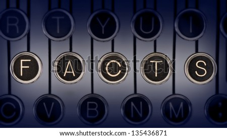 """Image of old typewriter keyboard with scratched chrome keys that spell out the word """"FACTS"""". Lighting and focus are centered on """"FACTS"""". - stock photo"""