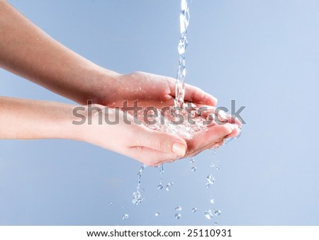 Image of open human palms under splashing water over blue background