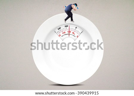 Image of overweight person try to lose weight by running on the scale shaped an empty plate - stock photo
