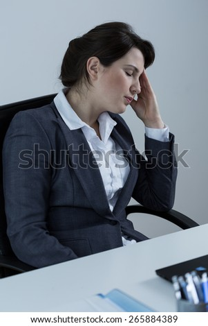 Image of overworked businesswoman sitting at the desk