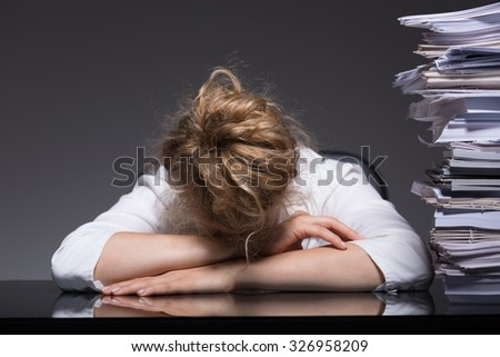 Image of overworked woman sleeping on desk at her workplace - stock photo