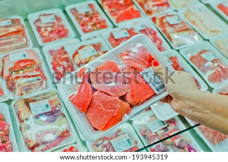 Image of packaged meat with woman hand in the supermarket - stock photo