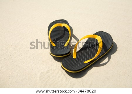 Image of pair of yellow and black flipflops on sandy beach - stock photo