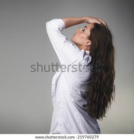 Image of passionate young brunette posing with her hands in hair against grey background - stock photo