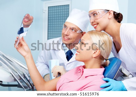 Image of patient holding mirror with doctor and assistant near by - stock photo