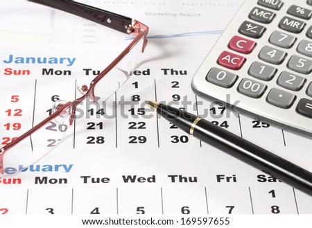 image of pen calculaton and glasses on calendar - stock photo