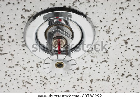 Image of pendent fire sprinkler in acoustic ceiling tile.  Fire sprinklers are part of an overall safety protocol for fire and life safety. - stock photo