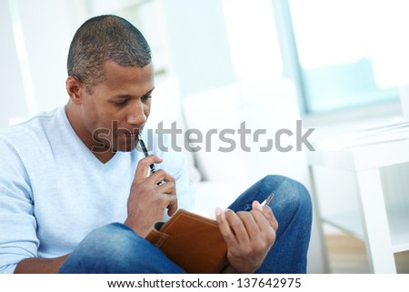 Image of pensive African man with notepad and pen - stock photo