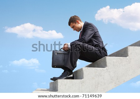 Image of pensive businessman sitting on stairs against blue sky