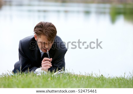 Image of pensive businessman with pen planning work while lying on green grass - stock photo