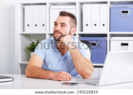 Image of pensive young businessman with notebook looking up in the office