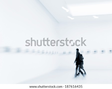 image of people in the lobby of a modern art center with a blurred background and blue tonality