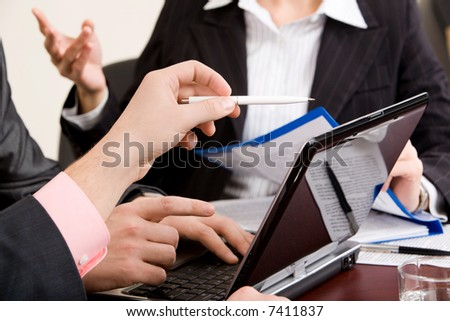 Image of people's hands pointing at monitor of laptop - stock photo