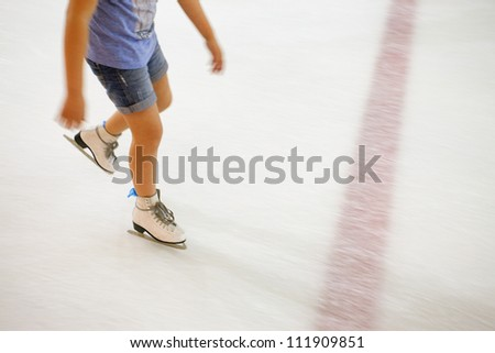 Image of people who are ice skating in the ice rink indoors. - stock photo