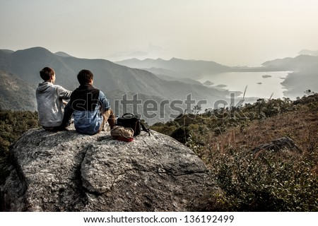 Image of people who are sitting on a big rock while looking far on the landscape - stock photo