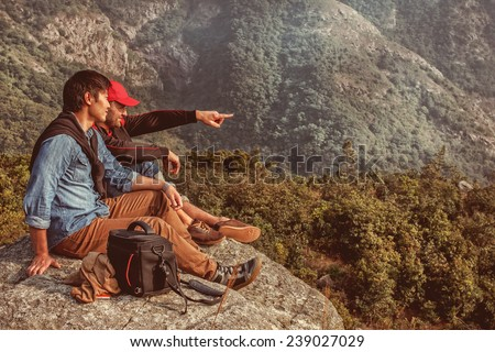 Image of people who are sitting on the cliff and looking on something - stock photo