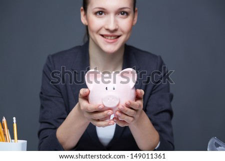 Image of pink piggy bank held by smiling female - stock photo