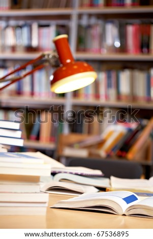 Image of place in library: table with lamp and books - stock photo