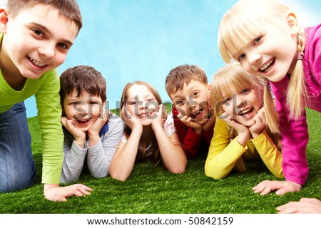 Image of playful children lying on a green grass and looking at camera - stock photo