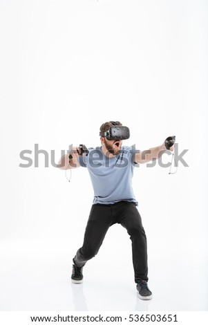 Image of playful young man wearing virtual reality device standing over white background and jumping.