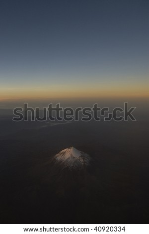 Image of PopocatépetlMexican Volcano taken from airplane showing sunrise and allowing for copy space - stock photo