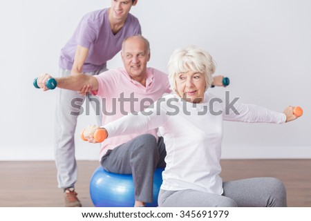 Image of positive seniors exercising at fitness studio