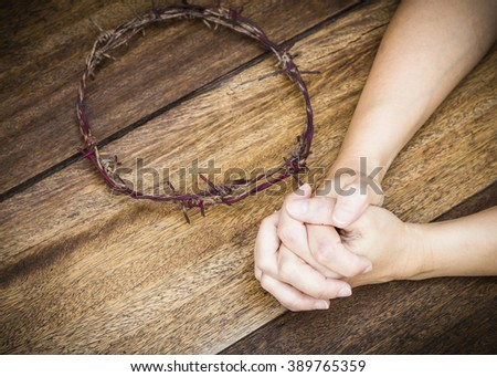 image of prayer  hands with  metal Barbed Wire made like the crown of thorns of Jesus on wooden background, Christian concept, Easter background with copy space - stock photo