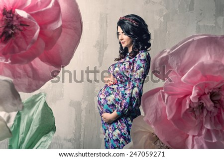 Image of pregnant woman touching her belly with hands - stock photo