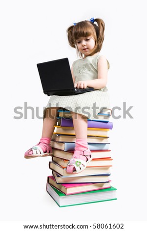 Image of preschooler sitting on the heap of books and working with laptop - stock photo