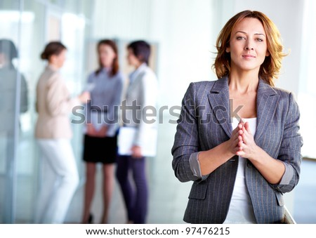 Image of pretty business leader looking at camera with interacting partners at background - stock photo