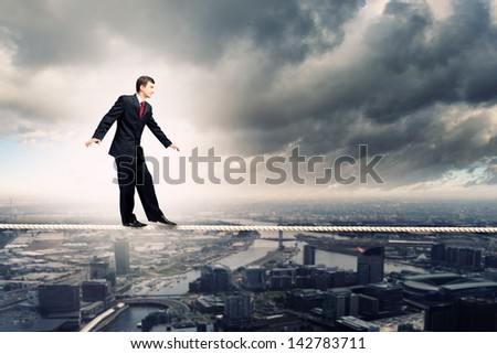 Image of pretty businessman balancing on rope - stock photo