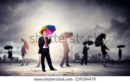 Image of pretty businessman with umbrella walking in crowd of people - stock photo