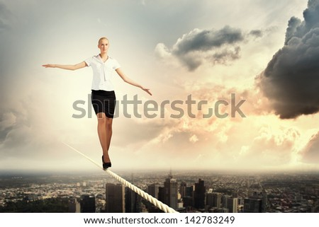 Image of pretty businesswoman balancing on rope - stock photo
