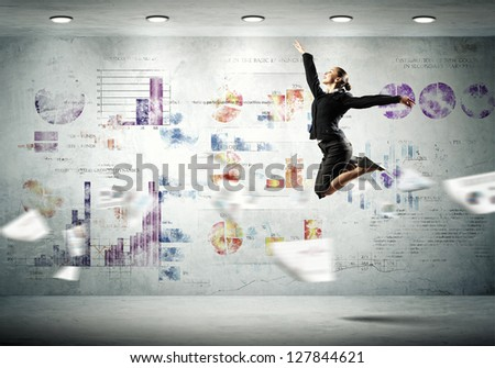 Image of pretty businesswoman jumping high against financial background - stock photo