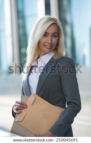 Image of pretty businesswoman looking at camera and holding documents outdoor - stock photo