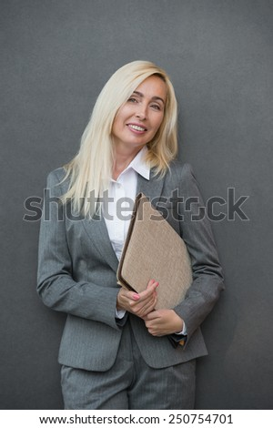 Image of pretty businesswoman standing near wall holding folder and looking away - stock photo