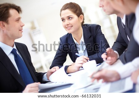 Image of pretty employee looking at business partner while discussing business plan at meeting