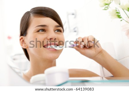 Image of pretty female brushing her teeth in front of mirror in the morning - stock photo