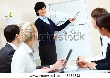 Image of pretty female looking at camera in working environment