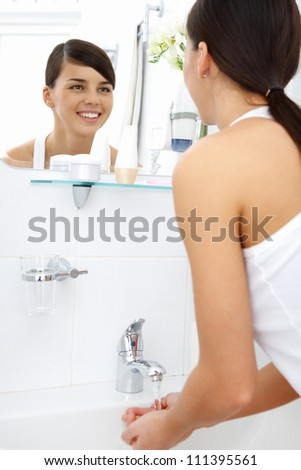 Image of pretty female looking in mirror while washing her hands in the morning - stock photo